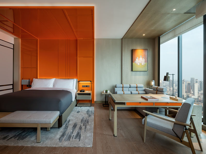 This modern hotel room features a bright orange headboard with hidden lighting, that wraps from behind the bed, up the wall, and onto the ceiling, creating a bold and colorful detail in the room that assists in making the room feel larger by drawing the eye upwards to the ceiling. #WrapAroundHeadboard #Headboard #Bedroom