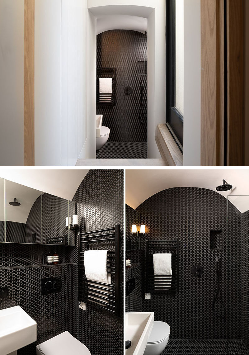 In this modern bathroom, black penny tiles cover the walls and floor, creating a bold and striking color contrast. #BlackBathroom #BlackPennyTiles