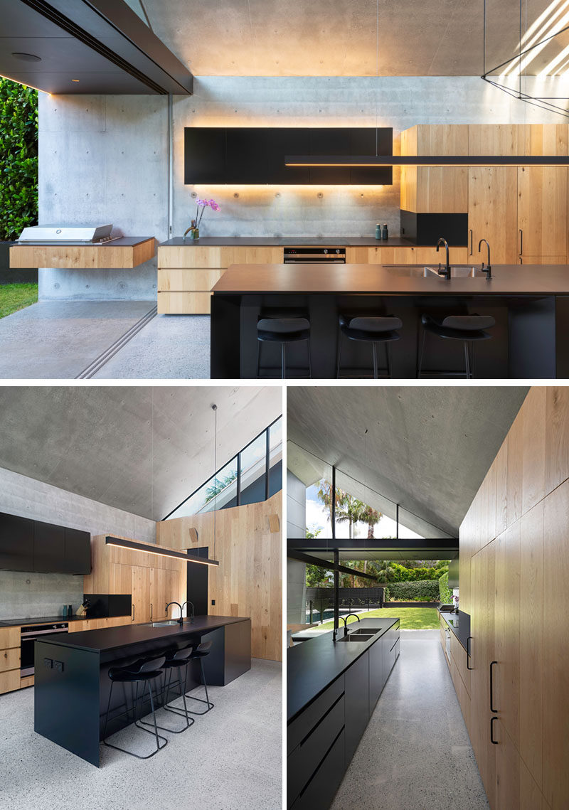 Matte black design elements, like the kitchen island, lighting, and window frames, contrast both the wood and concrete elements, and add a dramatic touch to the interior of this modern house. #KitchenDesign #BlackAndWoodKitchen #ModernKitchen