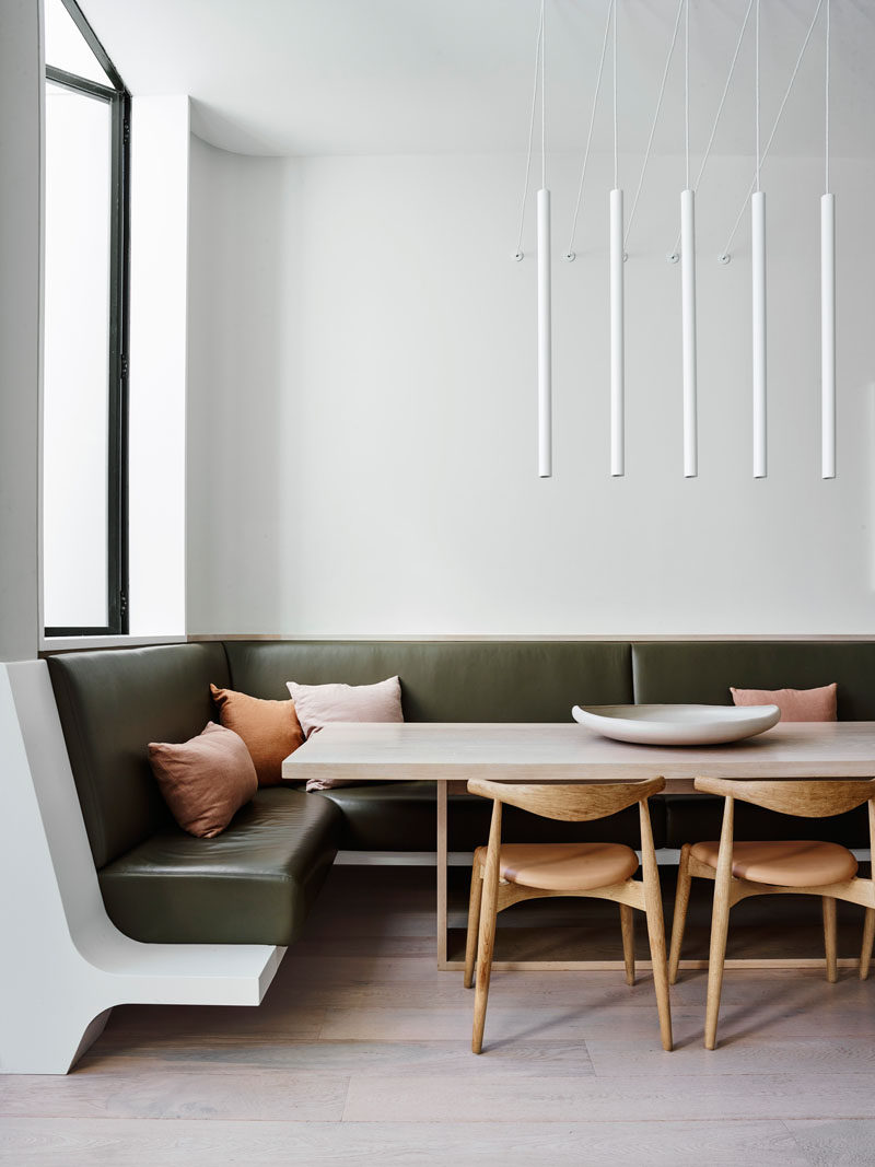 This modern dining area with minimalist white pendant lights, also features built-in seating in the form of a banquette that wraps around the corner. #DiningRoom #Banquette
