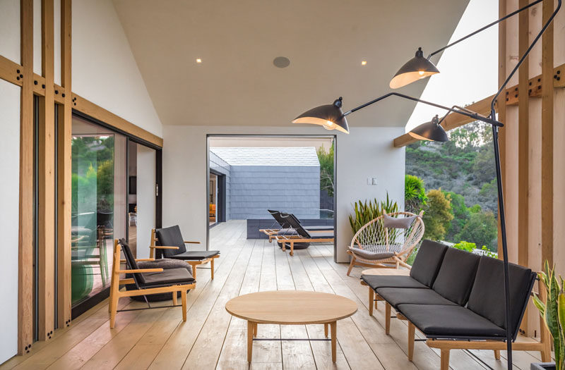 A covered area of this deck has been designated as a secondary living space, with armchairs, sofas, and lighting. #OutdoorSpace #OutdoorLivingRoom