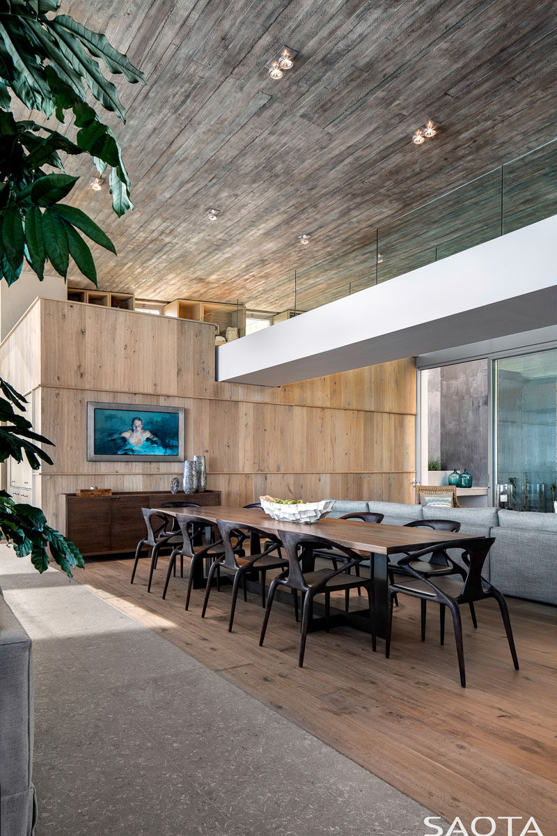 This large, modern dining area showcases the concrete ceiling and rough-sawn planks. #DiningRoom #ModernDining
