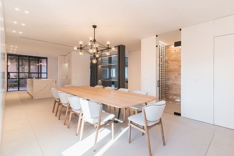In this modern dining room, a sculptural black chandelier hangs above a large wood dining table, that's surrounded by light grey upholstered dining chairs. #ModernDiningRoom #DiningRoom