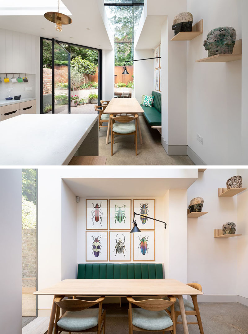 This rear house extension has a skylight that wraps from the ceiling down to a window, while green and wood banquette seating at the dining helps to provide a relaxed atmosphere. #DiningRoom #HouseExtension #Skylight
