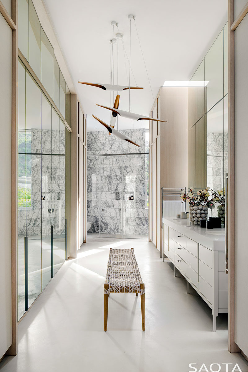 This master bathroom has a wall of mirrored wardrobes, a large vanity, and at the end is a walk-in shower, and hidden out of sight is a freestanding bathtub. #MasterBathroom #BathroomDesign