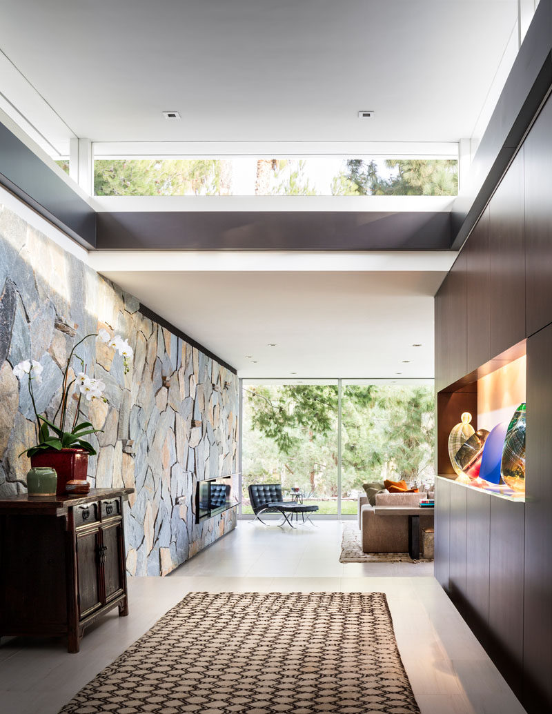 In this modern foyer, there's a Bouquet Canyon stone wall that connects with the living room. #StoneWall #Foyer #Entryway #Hallway