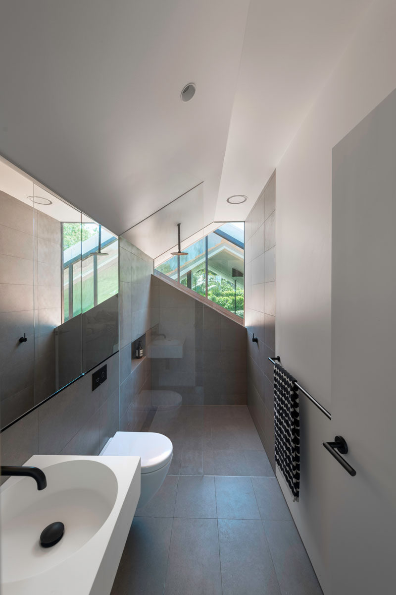 This modern bathroom has a walk-in shower, and an angled window that lets in natural light. #BathroomDesign #ModernBathroom