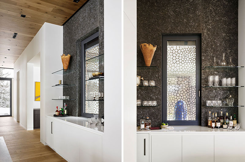 Adjacent to the kitchen in this modern guesthouse, is a bar area that highlights the metal screen outside, and makes use of glass shelving to display a variety of glassware. #Bar #HomeBar #Shelving