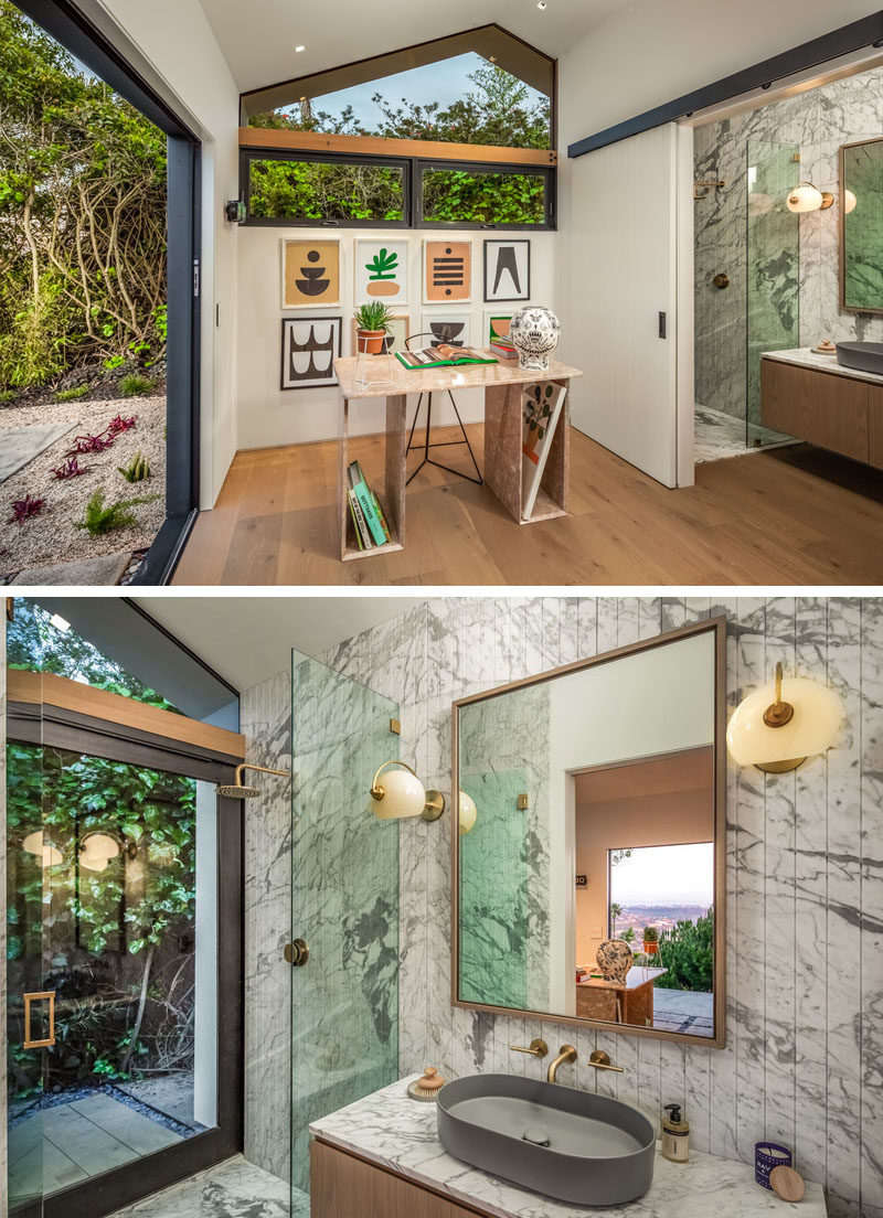 This modern house has a guest suite, currently being used as a home office. Behind a suspended sliding door is an ensuite bathroom, with a walk-in shower and a floating wood vanity. #GuestSuite #HomeOffice #EnsuiteBathroom #ModernBathroom