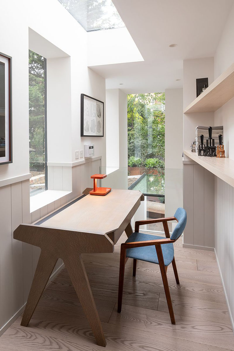 Skylights and windows provide an abundance of light to this modern home office, while light oiled ash flooring adds a natural touch. #HomeOffice #Skylights