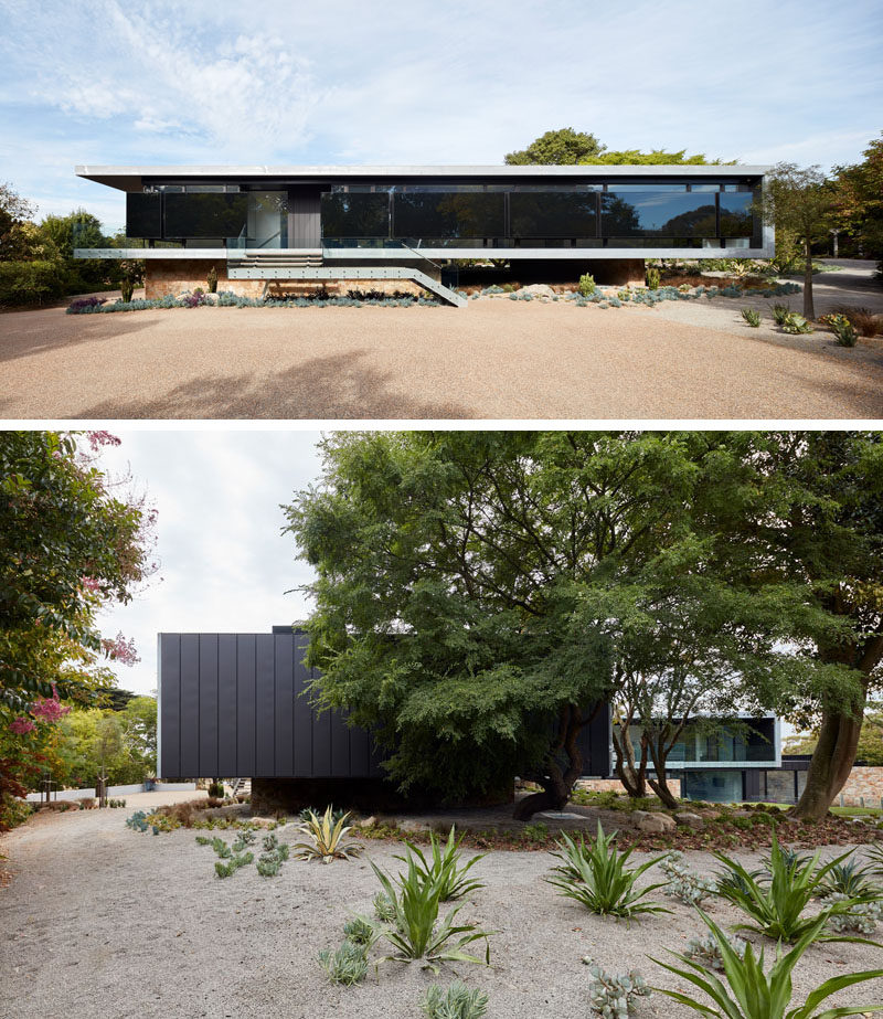 This modern house has walls of windows, however insulated black panels have been added for weather protection, as well as reflecting the silhouette of the established gardens. #ModernHouse #ModernArchitecture
