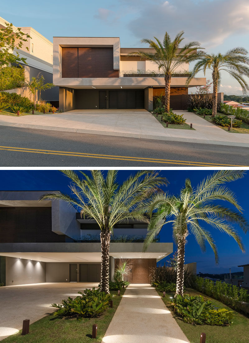 At the front of this modern house, landscaping with strategically placed lighting, highlights the driveway and the path to the front door. #Landscaping #OutdoorLighting #ModernHouse