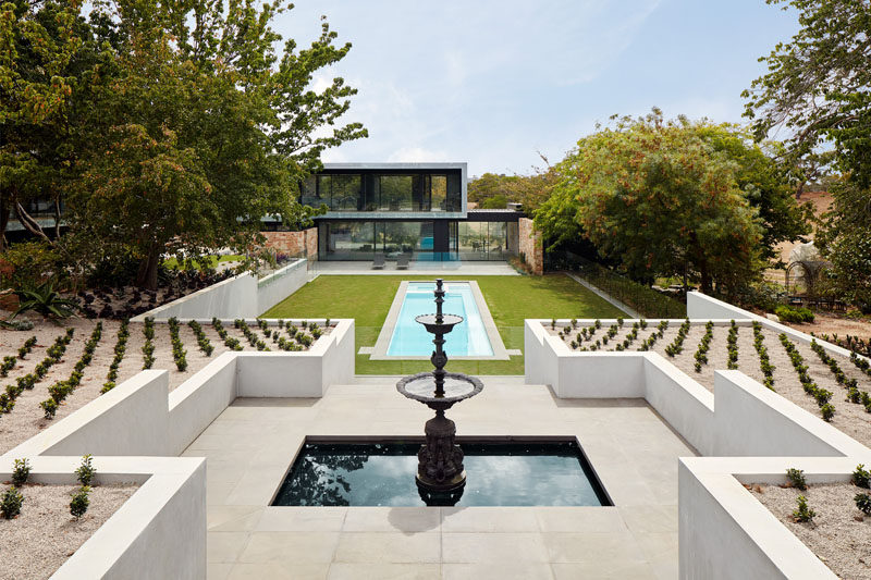 At the end of the pool are stairs that lead up to a fountain, while on either side of the fountain are perfectly arranged plants in a symmetrical pattern. #Landscaping #SwimmingPool #Fountain #Garden