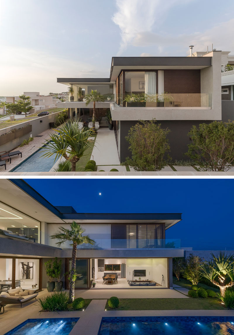 At the rear of this modern house, landscaping with palm trees and paths surrounds a swimming pool, that's the main focal point of the backyard. #SwimmingPool #ModernArchitecture #Backyard #Landscaping