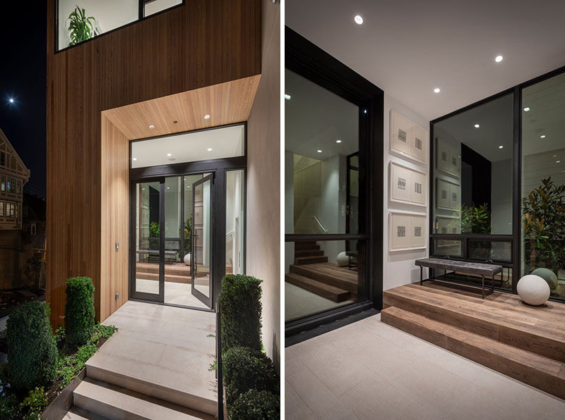 A small wood lined alcove welcomes visitors to this modern house, while just inside is a small hallway that leads to the great room. #Entryway #GlassFrontDoor