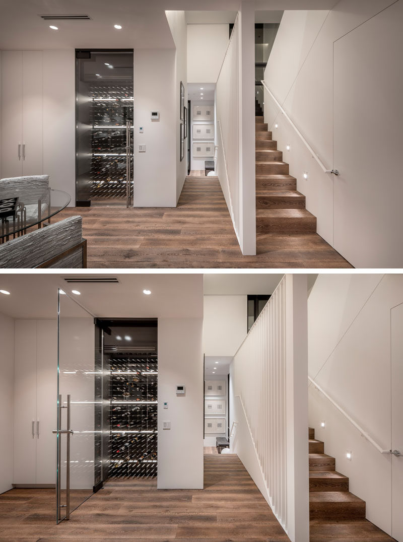 Featured throughout this modern house are a wide plank, long dimension engineered wood floors, that help to create a seamless appearance. A wine room with a pivoting glass door is located next to a closet and bathroom. #WoodFlooring #WineRoom #WineStorage