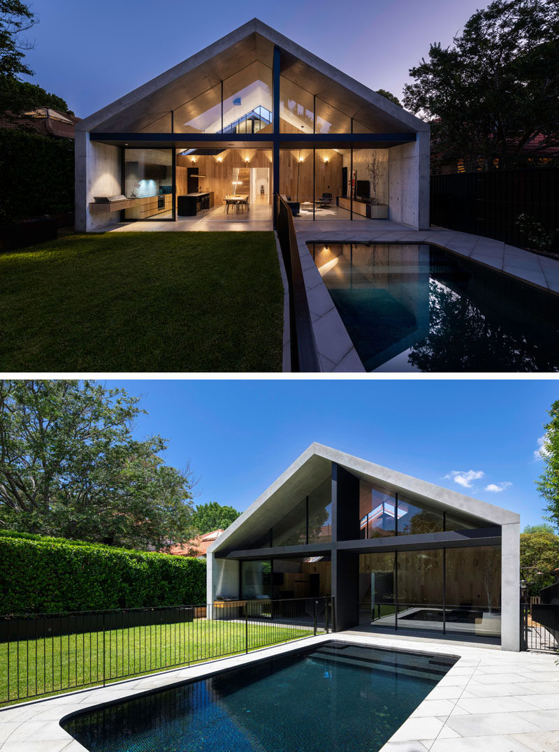 Large sliding glass doors open this modern house extension to a private backyard that's surrounded by hedges and is home to a grassy area and a swimming pool. #ModernHosueExtension #Backyard #Yard #SwimmingPool