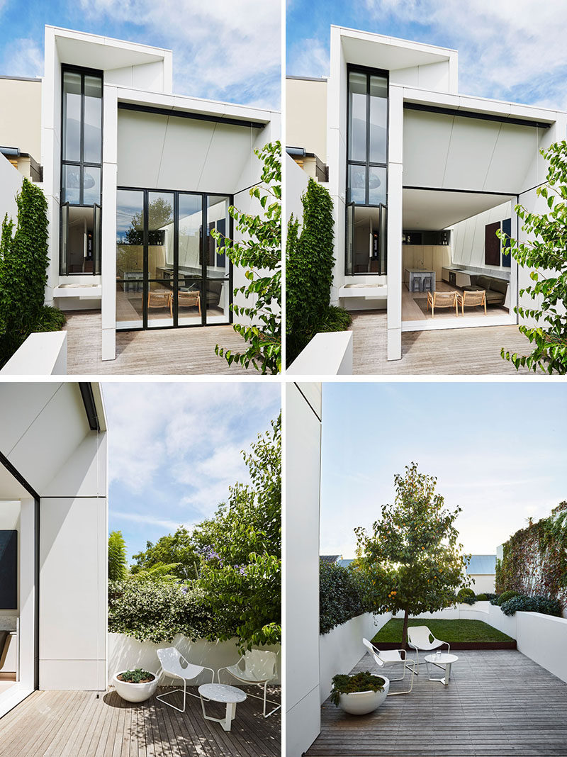 The modern extension features bi-fold pocket doors that hide away and open up the interior space to the terrace and grassed area beyond. #ModernExtension #Architecture #Landscaping #Backyard