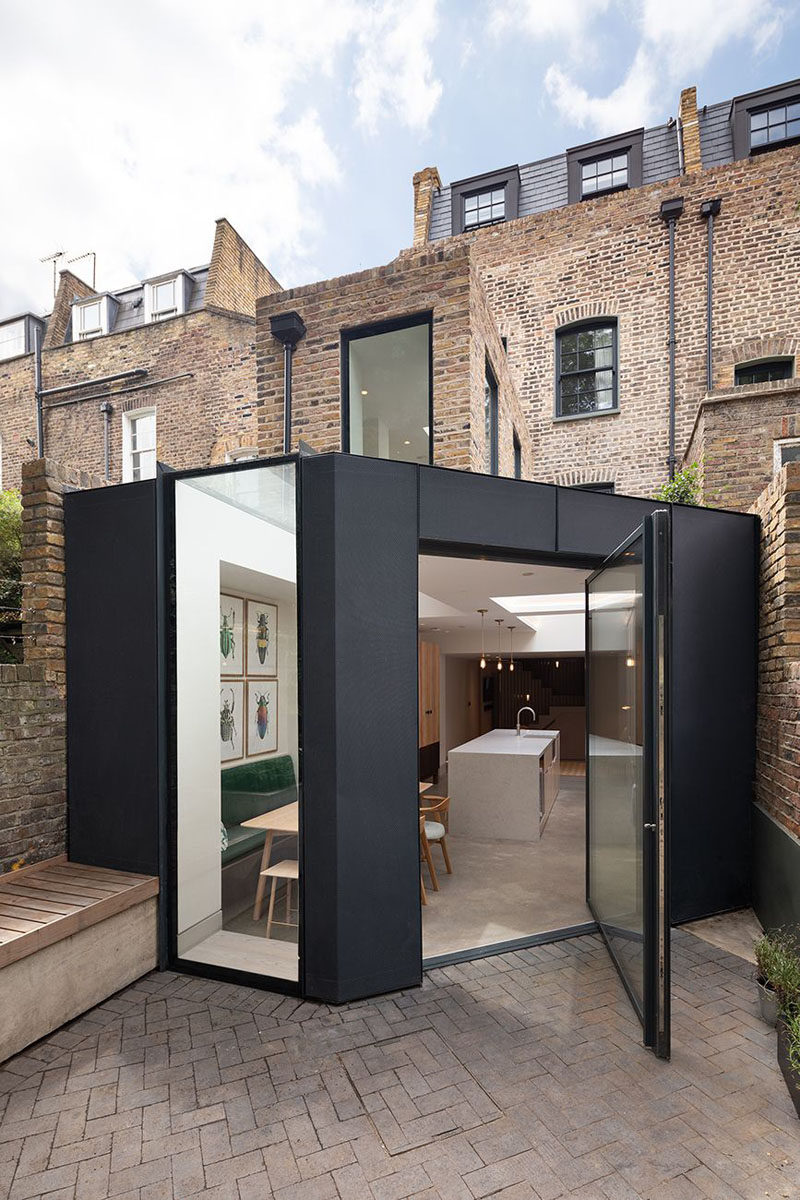 A large black-framed pivoting glass door connects the dining room and kitchen within this extension to the rear garden. #RearExtension #PivotingDoor