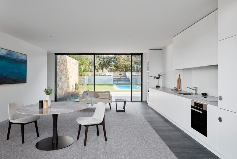 This modern home has a guest suite on the lower level of the house that features a kitchen that runs along the wall, and a view of the pool and a fountain in the distance. #GuestSuite #WhiteKitchen #MinimalistKitchen