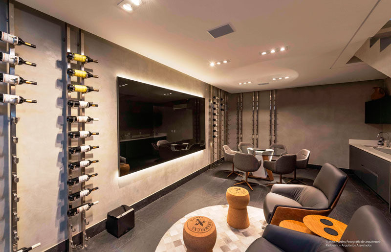 In this modern basement, there's a bar and lounge with a large television on the wall, and floor to ceiling wine racks to display the home owner's wine collection. #Basement #WineRack