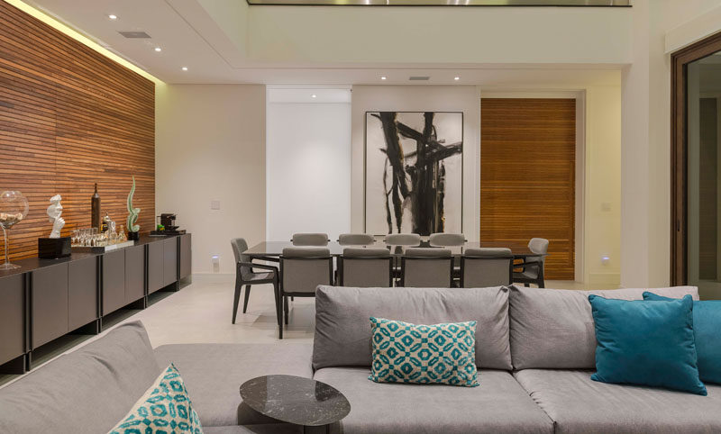 In this modern open plan interior, wood accent walls and artwork contrast the all white walls, while hidden lighting creates a calm atmosphere. #LivingRoom #DiningRoom #WoodAccentWalls