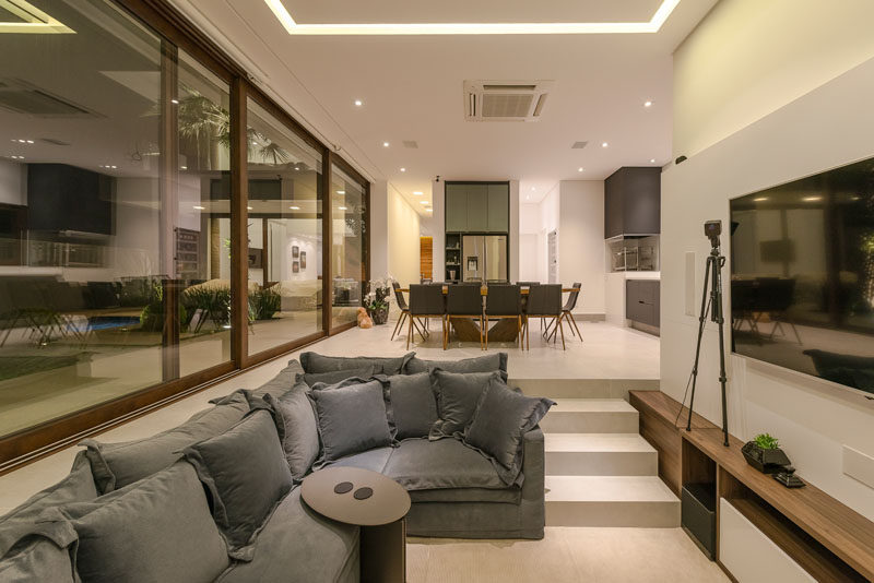 Large sliding glass walls open to connect the backyard to the interior living spaces of this modern house, like the open plan sunken living room, dining room, and kitchen. #SunkenLivingRoom #GlassWalls #DiningRoom