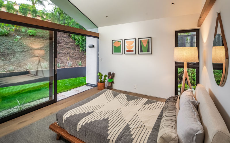 This modern bedroom has a large sliding glass door that opens to a small grassy area. #Bedroom #ModernBedroom #SlidingDoor
