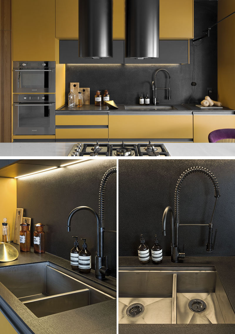 This modern kitchen has been named the 'Dijon Kitchen' due to the mustard cabinet color, while black accents like the backsplash, countertop, and faucet, complement the support structures of the island. #UndermountSink #KitchenDesign #ModernKitchen