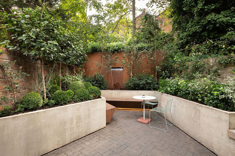 In this modern garden, custom-designed planters wrap around the patio, helping to create depth, while a small seating area and water feature are the focal point of the outdoor space. #ModernGarden #GardenDesign #Landscaping #LandscapeDesign
