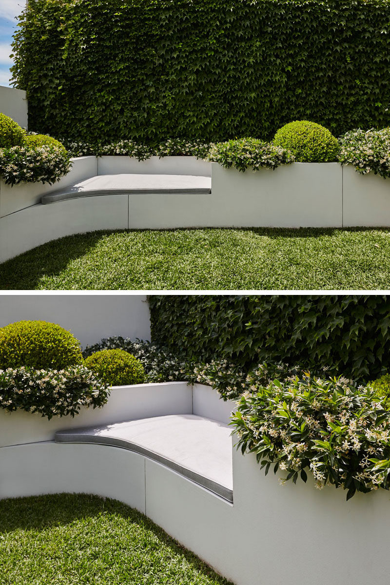 In this modern yard, a built-in seat has been included that provides a place for someone to relax next to the planters. #Landscaping #Backyard #BuiltInSeat #Planters