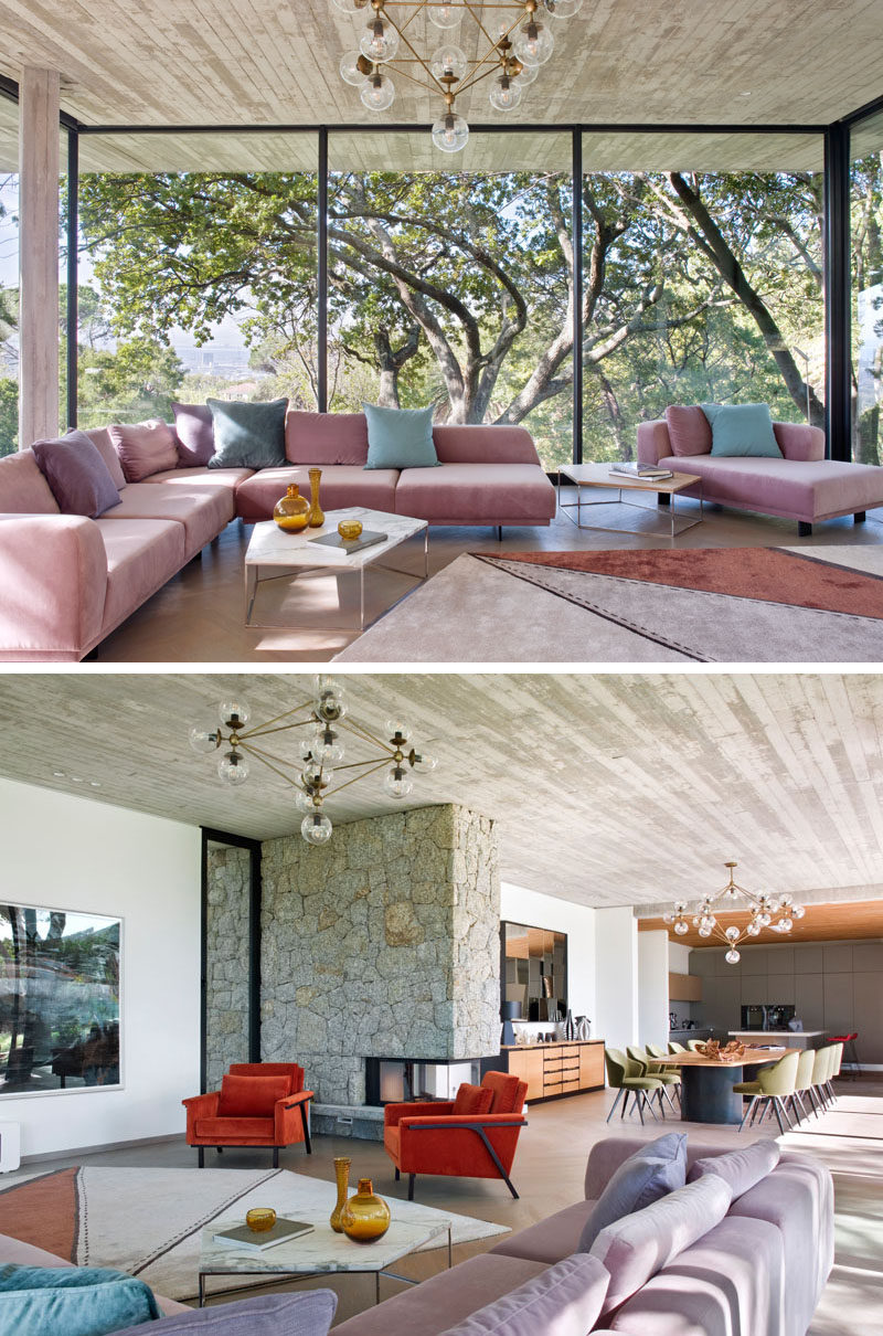 Inside this modern house, floor-to-ceiling windows provide a natural backdrop for the living room that features an L-shaped sofa with chaise, as well a pair of customized Maxx armchairs. A see-through fireplace has been embedded within a surround of rough-hewn granite. #ModernLivingRoom #ModernWindows #Fireplace