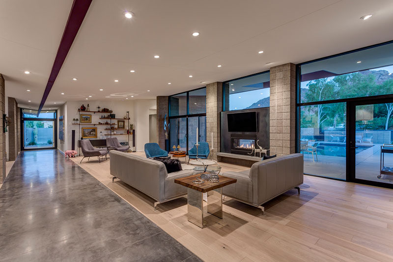 This modern living features a material palette of exposed beams, sandblasted block, concrete, stucco, wood floors, and glass. #LivingRoom #ModernLivingRoom