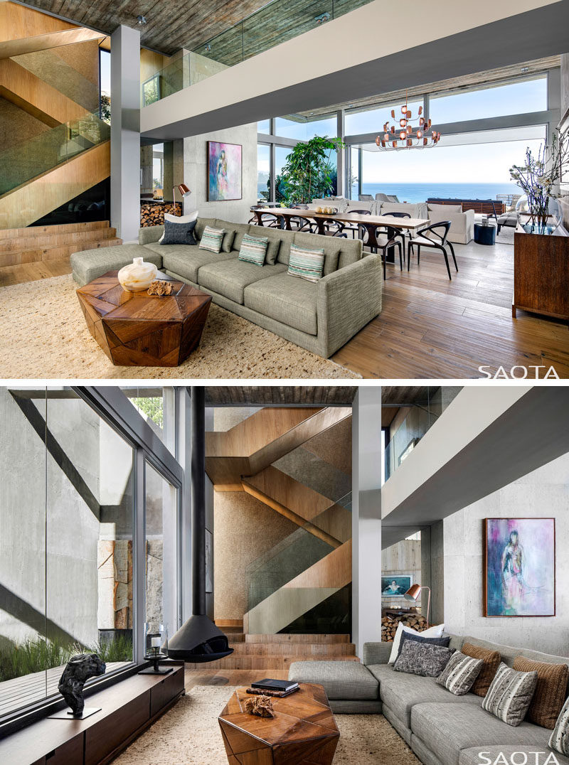 This open plan modern interior has a living room with large windows, a hanging fireplace, and a view of the wood-clad stairs. #LivingRoom #Stairs
