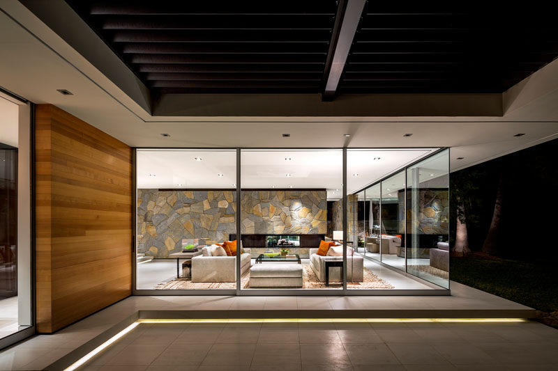 Floor to ceiling windows wrap around this modern living room, while a linear fireplace has been installed within the stone wall. #LivingRoom #StoneWall #ModernLivingRoom #GlassWalls