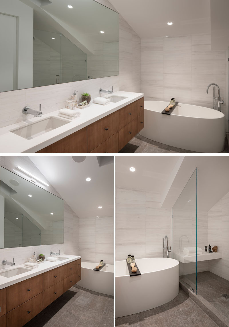 In this modern master bathroom, a large mirror reflects the light throughout the room, while the freestanding bathtub sits against the wall, and the shower is tucked away in an alcove opposite the vanity. #MasterBathroom #ModernBathroom #BathroomDesign