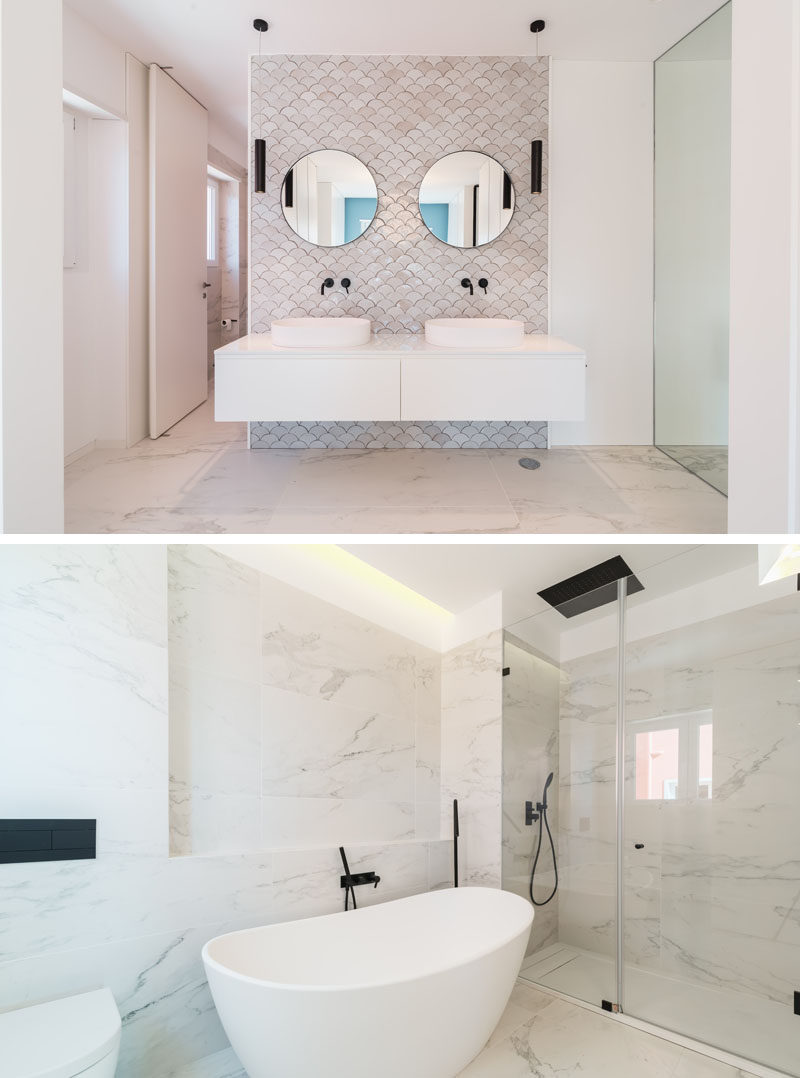 In this modern master bathroom, a decorative fish-scale tile pattern highlights the vanity, while on the opposite wall, a freestanding bathtub is the focal point. #MasterBathroom #ModernBathroom