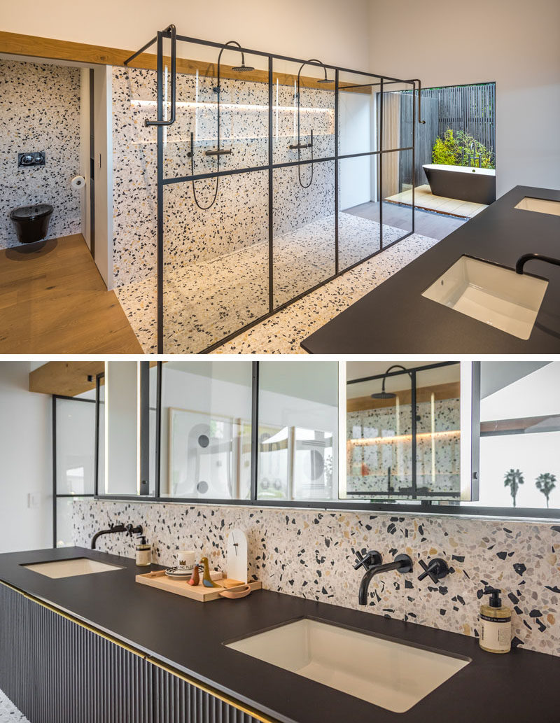 In this modern ensuite master bathroom, there's a two-person shower with a black-framed glass shower screen, while the freestanding bathtub is located outside in an area with privacy screens and plants. #ModernBathroom #EnsuiteBathroom #MasterBathroom