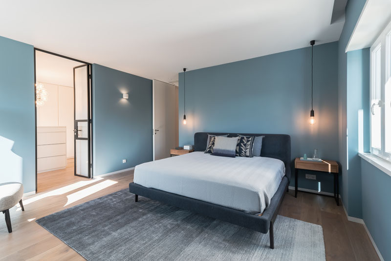 In this modern master bedroom, the designers decided to paint the walls in a sophisticated blue, to provide a special contrast from the other spaces in the apartment. #BlueBedroom #BedroomDesign #ModernBedroom