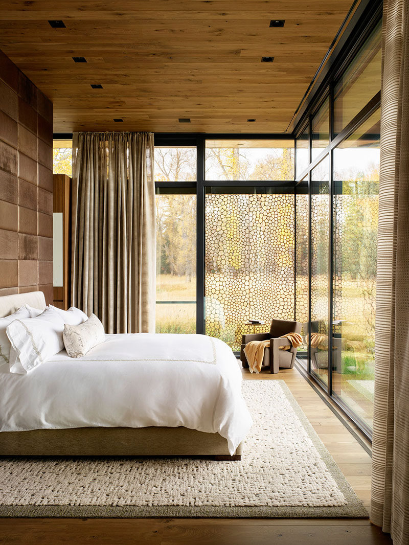This modern bedroom features floor-to-ceiling windows, creating a private nature experience. #ModernBedroom #BedroomDesign