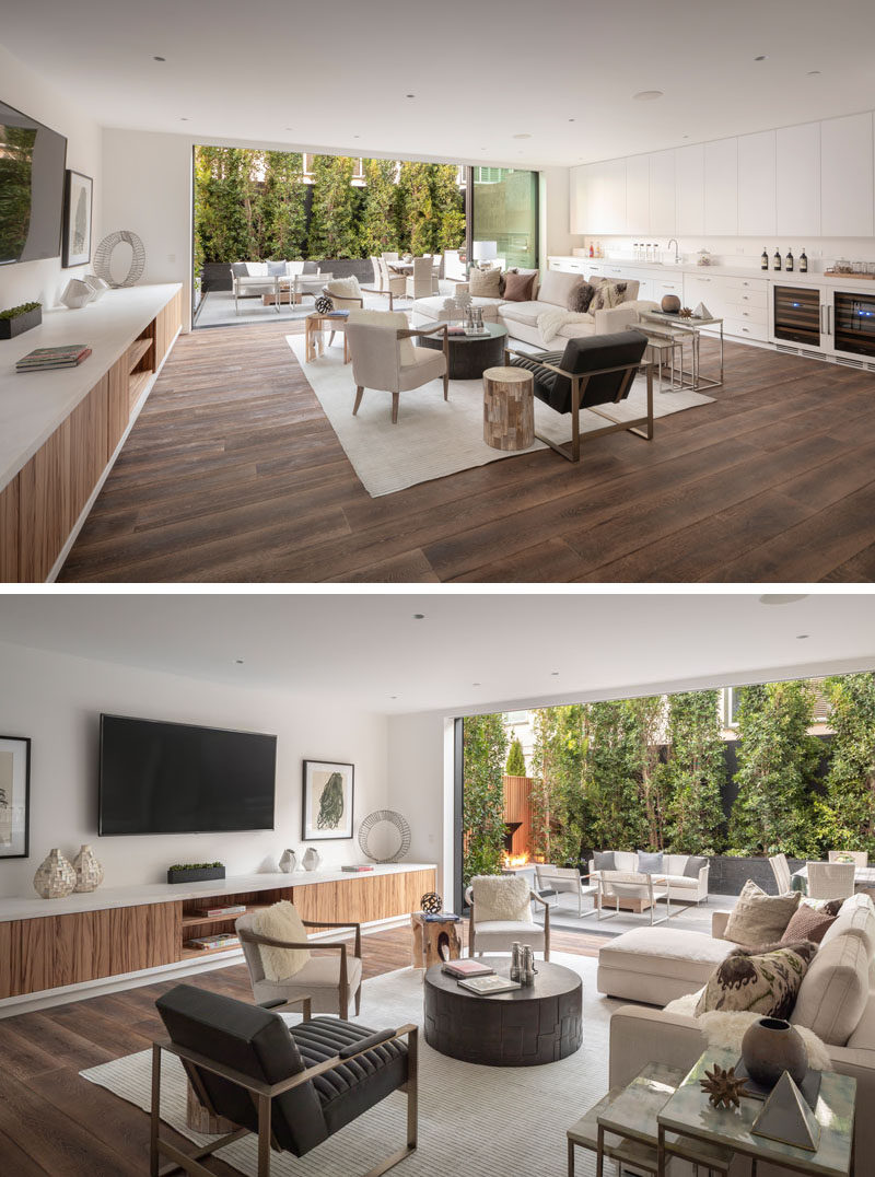 This modern and oversized great room features floor-to-ceiling windows that open to provide access to a patio.Red Gum was selected as an accenting wood on the first floor, and is used on the cabinetry that runs along the wall. #GreatRoom #ModernInterior #LivingRoom