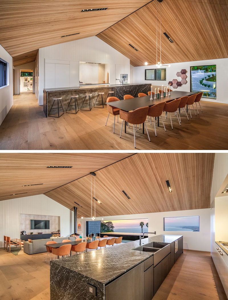 The social areas of this modern house are open plan, with the living room, dining room, and kitchen all sharing the same space. The wood ceiling helps to draw the eye upwards, and adds to the feeling of it being like a farmhouse. #ModernInterior #WoodCeiling #OpenPlanInterior
