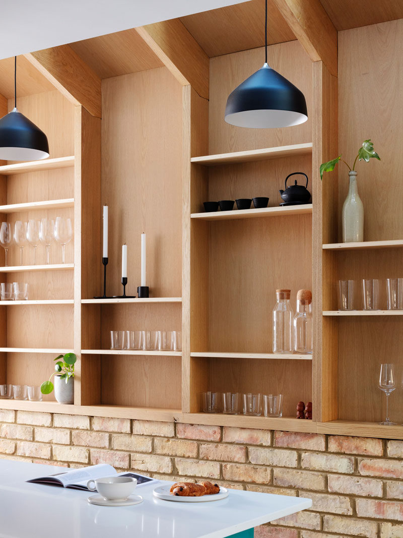 Running along the wall in this house, is a custom-designed wood wall pantry, with shelving and black pendant lights. #WallPantry #Pantry #InteriorDesign