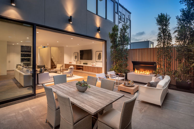 This modern patio is poised for entertaining, with an outdoor dining area and lounge. Beside the seating area is a remote controlled fireplace, creating a space that can be used during the day and into the night. #ModernPatio #OutdoorFireplace