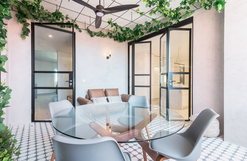 This modern apartment has a winter garden, with a sitting area, a dining area, and plants that will grow to create a green ceiling. #SittingArea #InteriorDesign