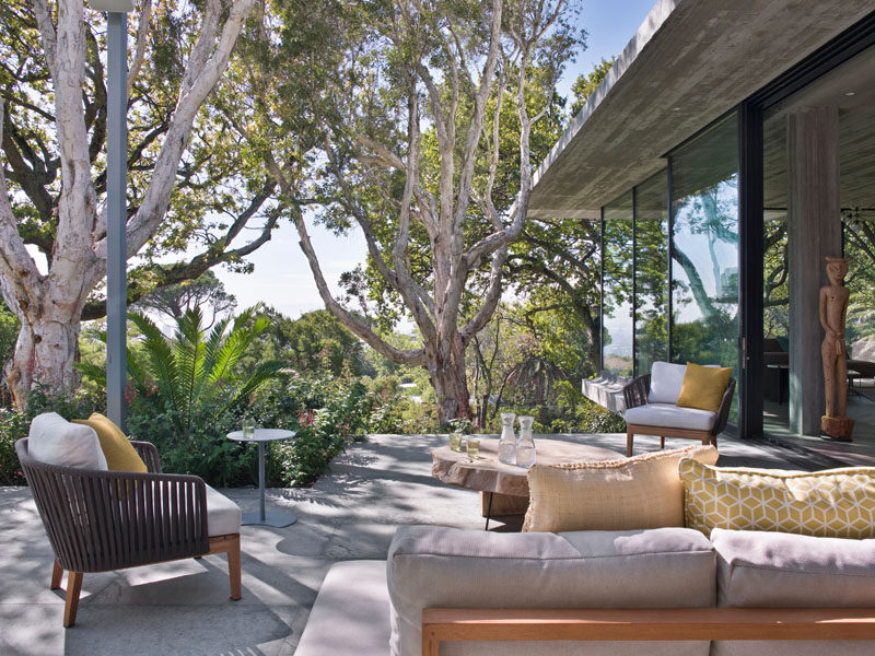 Sliding glass doors open the social areas of this modern house to a patio that take advantage of the views and mature trees that surround the property. #OutdoorSpace #ModernPatio