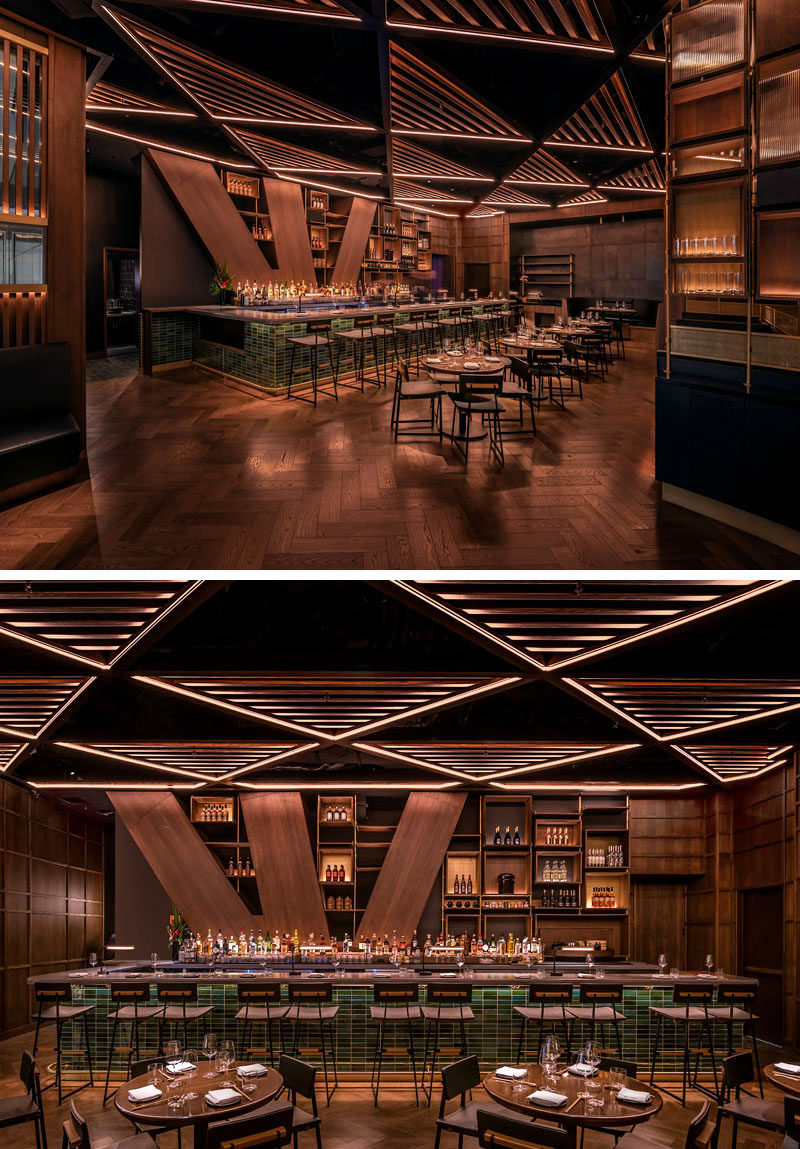 The trellis' alternating patterns of open and slatted triangular surfaces in this restaurant, help to conceal the acoustical and lighting systems, while also acting as a unifying element that draws guests into the heart of the interior. #RestaurantDesign #BarDesign #RestaurantCeiling