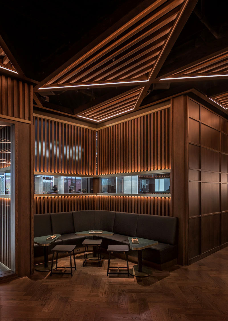 A rich palette of dark stained oak with satin brass, black metal, and textured glass detailing, greets patrons as they step inside the restaurant. #RestaurantDesign #RestaurantInterior