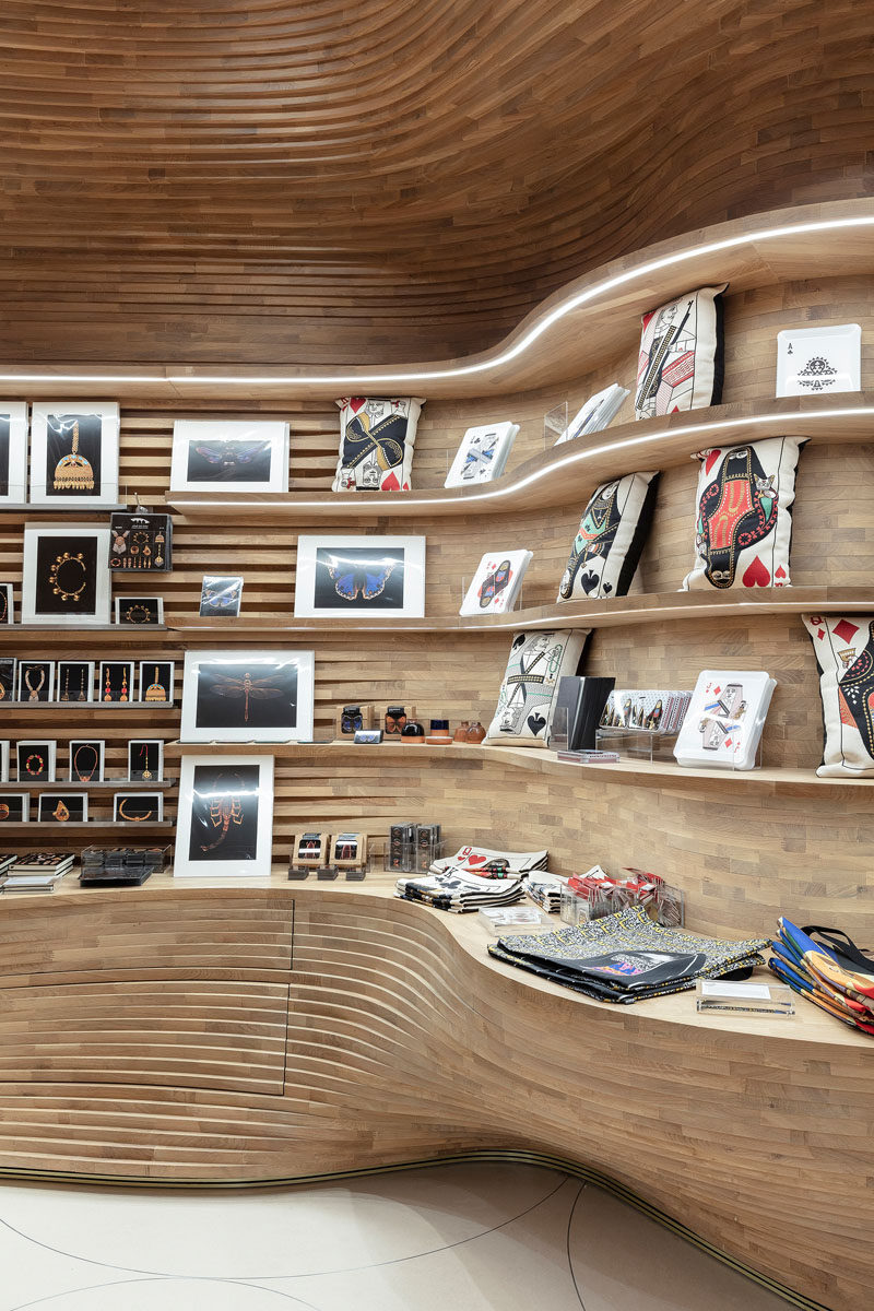 Inspired by a cave, the design of the gift shop at the National Museum of Qatar features 40,000 wood pieces that create a cave-like interior. #RetailDesign #RetailStore #ModernStore #Wood #Shelving