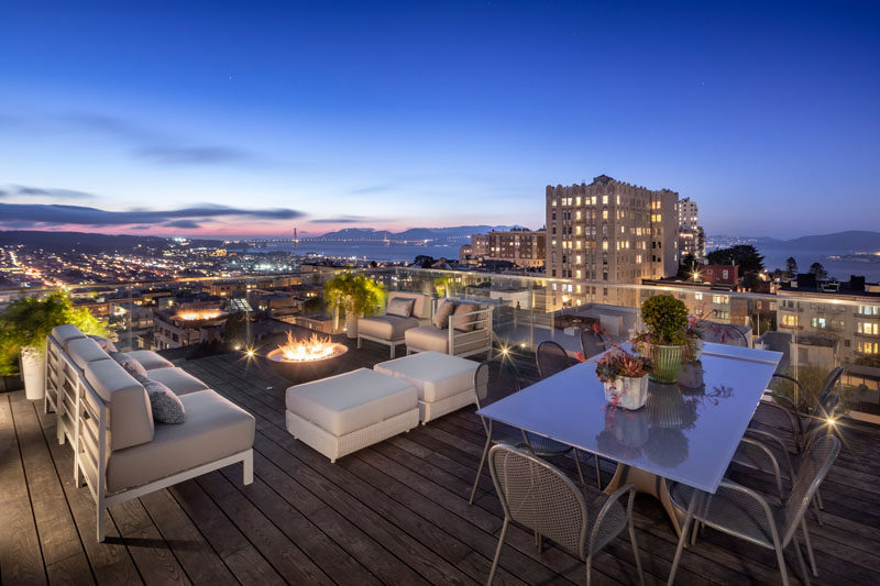 This modern rooftop deck has a lounge area with a fireplace, and a dedicated area for alfresco dining. #RooftopDeck